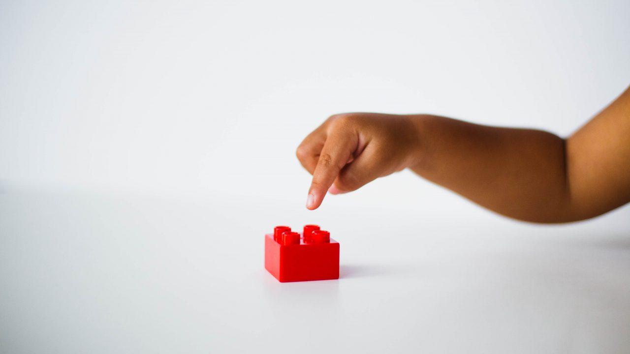 child pointing to red interlocking brick toy