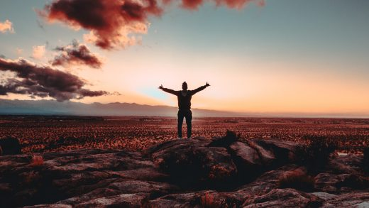 person standing on rock raising both hands